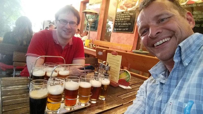 two guys drinking flights of beer in prague