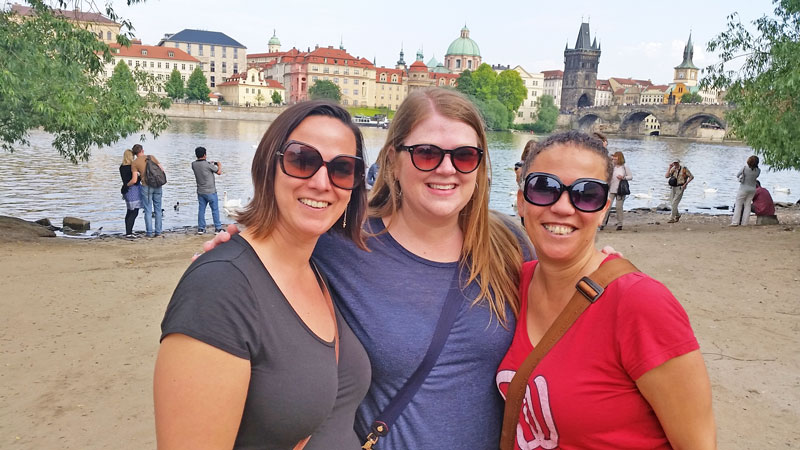 3 girls by the prague riverside with charles bridge in background