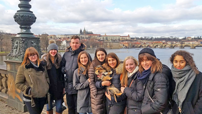 group standing by the riverside with prague castle in the background