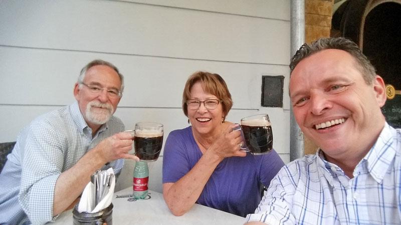 couple sitting down drinking dark beer in prague