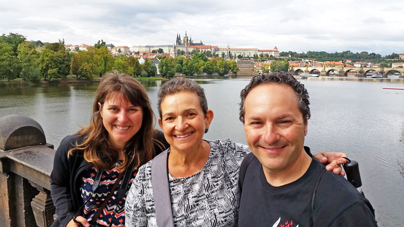 3 people standing on a bridge with prague castle and river in background